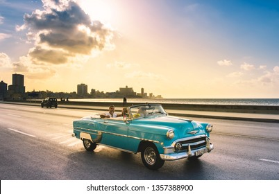 Havana, Cuba - October 04, 2018: American red 1956 Chevrolet blue mint Bel Air convertible vintage car with tourists on the Malecon in the evening sun in Havana City Cuba - Serie Cuba Reportage