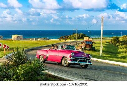 Havana, Cuba - October 04, 2018: American pink 1954 Chevrolet Bel air convertible vintage car with laughter cuban people on the fortress el Morro near the beach in Havana Cuba - Serie Cuba Reportage