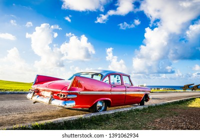 Havana, Cuba - October 04, 2018: HDR - American red 1959 Plymouth Fury vintage car parked on the fortress el Morro near the beach in Havana Cuba - Serie Cuba Reportage