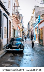 HAVANA, CUBA - OCTOBER 14, 2018: American black vintage car parked on a narrow cobblestone street leading to the Obispo Street in Old Havana in Cuba, with some incidental local people to be seen.