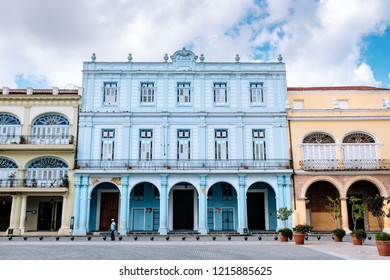 HAVANA, CUBA – OCTOBER 14, 2018: Colourful residences around the 16th-century colonial  Plaza Vieja square in Old Havana in Cuba, with some incidental local people to be seen.