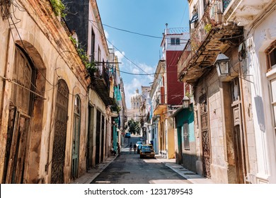 HAVANA, CUBA – OCTOBER 14, 2018: American black vintage car parked on a narrow cobblestone street leading to the Obispo Street in Old Havana in Cuba, with some incidental local people to be seen.