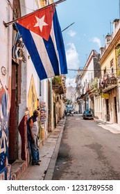 HAVANA, CUBA - OCTOBER 14, 2018: Cuban flag on a narrow cobblestone street leading to the Obispo Street in Old Havana in Cuba, with some incidental local people to be seen.