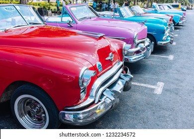 HAVANA, CUBA - OCTOBER 14, 2018: American colourful vintage convertible cars parked on a wide street in Old Havana, Cuba.