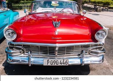 HAVANA, CUBA - OCTOBER 14, 2018: American red vintage convertible car parked on a wide street in Old Havana, Cuba.