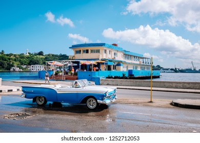 HAVANA, CUBA - OCTOBER 14, 2018: American blue vintage car driving along the road by the bay in Old Havana, Cuba, with some incidental local people to be seen and El Cristo in the background.