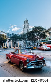 HAVANA, CUBA - OCTOBER 18, 2018: Red vintage car in the Plaza de San Francisco square in Old Havana in Cuba, with some incidental local people to be seen.