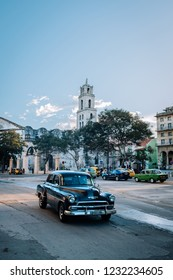 HAVANA, CUBA - OCTOBER 18, 2018: Black vintage car in the Plaza de San Francisco square in Old Havana in Cuba, with some incidental local people to be seen.