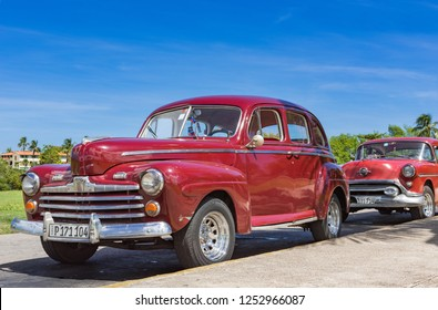 Havana, Cuba - October 21, 2017: American red brown Ford and Oldsmobile vintage cars parked under blue sky near the beach in Havana Cuba - Serie Cuba Reportage
