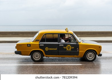 HAVANA, CUBA - OCTOBER 21, 2017: Old Car in Havana, Cuba. Retro Vehicle Usually Using As A Taxi For Local People and Tourist. Caribbean Sea in Background. Yellow Color Lada Taxi