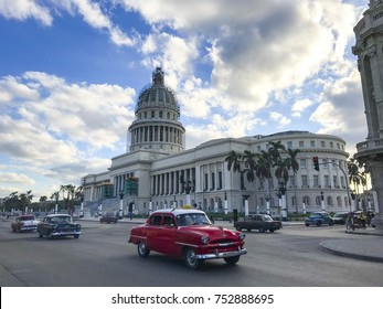 HAVANA, CUBA - OCTOBER 25, 2017: Red retro car cabriolet is riding on the crossroad near building of Capitol in Havana street at summer cloudy day