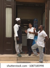 Havana, Cuba, October 28, 2016: Black men are arguing, standing on the stairs at the entrance to the cafe. Cook, an employee and a rich Latino with a smartphone and a gold watch