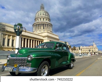 HAVANA, CUBA – OCTOBER 30, 2017: Vintage classic American car Dodge in main street Paseo Marti / Marti Promenade in front of El Capitolio against dark cloudy sky in Habana Vieja / Old Havana, Cuba