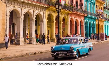 Havana, Cuba on December 22, 2015: A blue oldtimer taxi is driving through Habana Vieja in front of a colorful facade