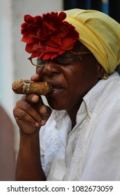 Havana, Cuba - Sep 9th 2017:African American woman sitting on the street of Havana and smoking cigar