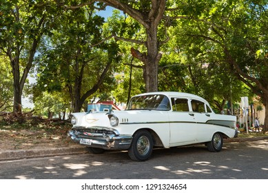 Havana, Cuba - September 24, 2018: American white 1957 Chevrolet Bel air vintage car parked in the shadow under a tree in Havana City Cuba - Serie Cuba Reportage