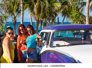 Havana, Cuba - September 28, 2018: Cuban latinas posing on the american blue white Ford Fairlane vintage car direct on the beach in Varadero Cuba - Serie Cuba Reportage
