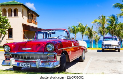 Havana, Cuba - September 28, 2018: American 1955 red Chevrolet Bel air convertible vintage car parked direct on the beach with a Ford Fairlane in the background in Havana Cuba - Serie Cuba Reportage