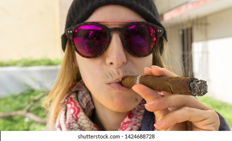 Havana, Cuba-December 2017: Beautiful woman, standing on the streets of Havana and enjoying fine Cuban cigar. Looking stylish, wearing a hat and sunglasses on a beautiful sunny day. Cuban signature.