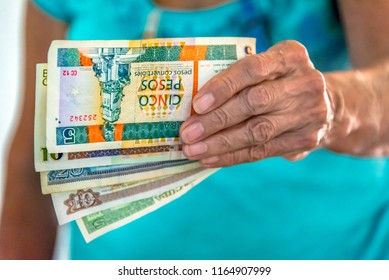 Havana, Cuba-July 18,2018: Hand of a senior woman holding the two currencies circulating in the country. One is equivalent to the USD, the other is for buying in the state and private food markets