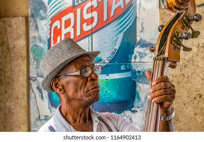 Havana, Cuba-July 20, 2018: Elder Afro-Caribbean Cuban man playing the acoustic bass in a bar in Old Havana. Self employment is booming in the Caribbean island after economic changes