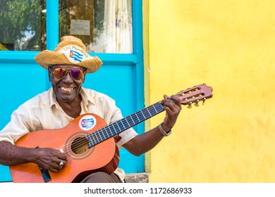 Havana, Cuba-July 9, 2018: Cuban man playing the acoustic guitar as a way of earning his life in Old Havana. The place is a Unesco World Heritage Site