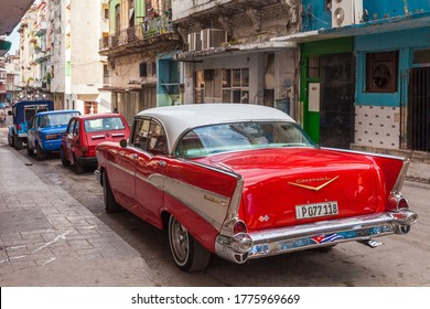 Havana, Cuba-October 07, 2016. Classic, old style, vintage, American red car parked on the narrow street on October 07, 2016 at historical old part of Havana City, capital of Cuba.