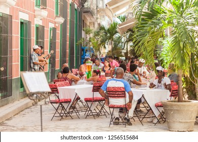 Havana, Cuba-October 8, 2016. People are sitting at the restaurant on the street and enjoys their time and listens to the local musicians on October 8 2016 at the old part of La Habana, Cuba.