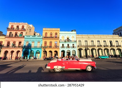 HAVANA - FEB 5: Classic red Car in  Old Havana main street, on February 5th, 2015 Havana, Cuba.Old cars and the UNESCO protected part of Old City are attracting millions of tourists every year