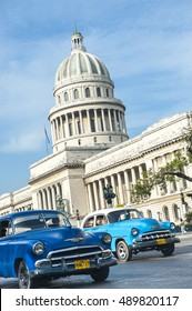 HAVANA - JUNE, 2011: Classic American Cuban taxi cars pass in front of the Capitolio building in Central Havana.