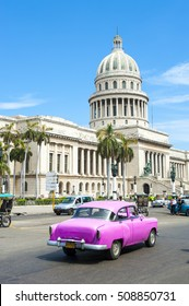 HAVANA - JUNE, 2011: Classic American Cuban taxi car passes in front of the Capitolio building in Central Havana.