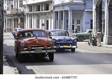 HAVANA - MARCH 30 2008: Classic American cars driving down road at Old town Havana, Cuba on March 30 2008.