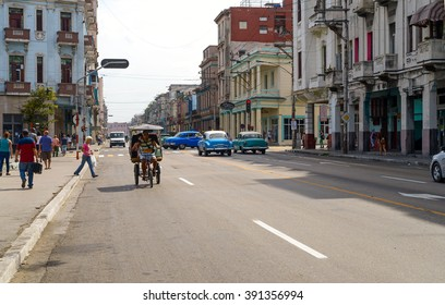 HAVANA - MARCH 7: Pedestrians and cars on one of the main streets in New Havana section, west of Prado Boulevard on March 7, 2016.