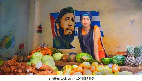 Havana Streets /Cuba - January 20,2018: The beautiful woman is posing in front of Fidel's poster in the market at Havana, Cuba