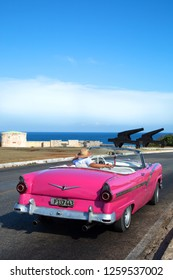 HAVANA-CUBA- DEC 4, 2018:  A classic convertible American vintage car in pink in Havana in Cuba.  They are very pride in having survived an era of no spare car parts and protecting their beauties.