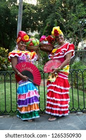 HAVANA-CUBA- DEC 4, 2018: Two Cuban woman wearing colorful cultural clothes and holding bowl of fruits and open fans