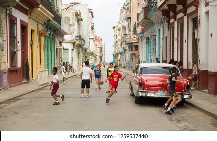 HAVANA-CUBA- DEC 5, 2018: Kids playing ball in the street in Centro Habana, one of the 15 municipalities or boroughs in the city of Havana, Cuba.