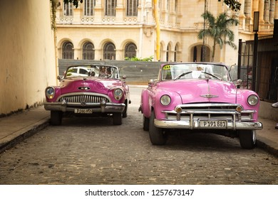 HAVANA-CUBA- DEC 5, 2018: Two retro  american classic cars in pink in Old Havana street,  These car owners can truly take pride in having survived an era of no spare car parts and protecting their be