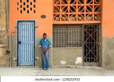 HAVANA-CUBA- DEC 7, 2018:  Proud man in blue suit posing in front of his orange house in Centro Havana one of the 15 municipalities or boroughs  in the city of Havana, Cuba