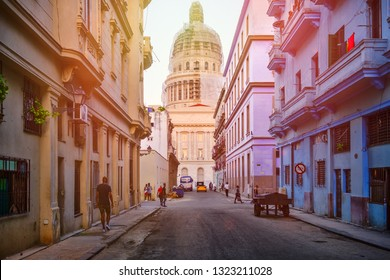 HAVANA,CUBA - FEBRUARY 23,2019 : Colorful street in Old Havana at sunset with the Capitol building on the background
