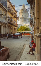 HAVANA,CUBA - FEBRUARY 23,2019 : Urban scene with people and old cars in Havana with the Capitol on the background