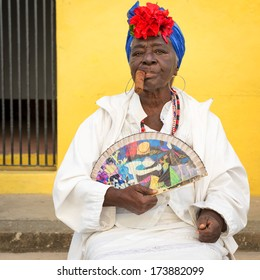 HAVANA,CUBA - JANUARY 20, 2014:Old black lady smoking a huge cuban cigar and wearing a typical dress with afrocuban religious necklaces