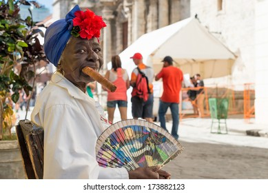 HAVANA,CUBA - JANUARY 20, 2014:Old black lady smoking a huge cuban cigar next to the havana Cathedral.Characters like this are a common sight in the streets of Old Havana
