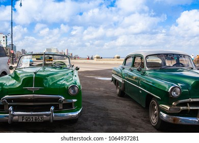 Havana,Cuba - January 22,2017: Old american cars on the road in Havana Malecon. The Malecon  is a broad esplanade, roadway and seawall which stretches for 8 km (5 miles) along the coast in Havana