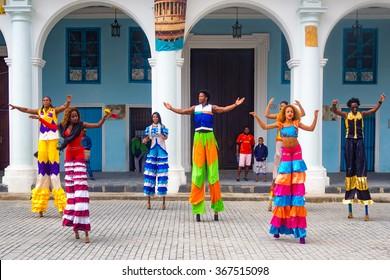 HAVANA,CUBA- JANUARY 24,2015 : Colorful band of street dancers on stilts on a beautiful Old Havana square