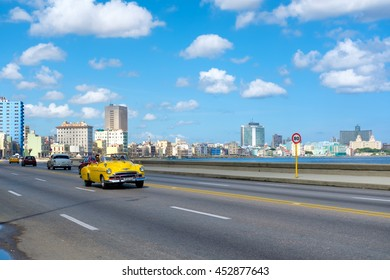 HAVANA,CUBA - JULY 14,2016 :  Street scene with old convertible car on the Havana malecon avenue with a view of the sea and the city skyline