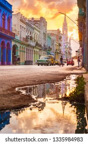 HAVANA,CUBA - MARCH 10,2019 :  Street scene with sunset and old cars in downtown Havana