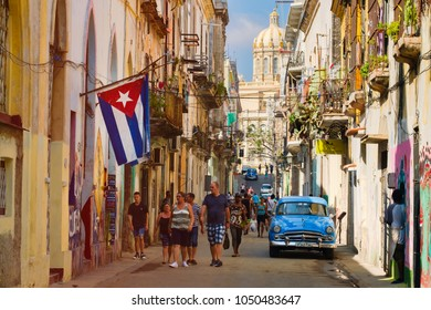 HAVANA,CUBA - MARCH 16,2018 : Street scene with cuban flag and classic car in Old Havana
