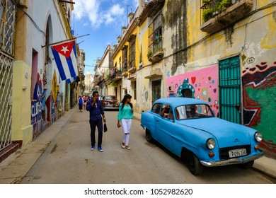HAVANA,CUBA - MARCH 16,2018 : Street scene with cuban flags, old car and colorful aged buildings in Old Havana