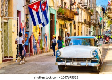 HAVANA,CUBA - MARCH 16,2018 : Urban scene with cuban flags, classic car and colorful decaying buildings in Old Havana